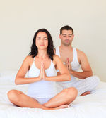 Couple doing yoga in bed — Stock Photo