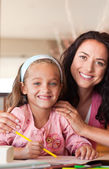 Happy mother helping her daughter for homework — Foto Stock