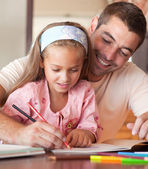 Cheerful father helping her daughter for homework — Стоковое фото