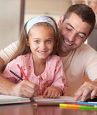 Cheerful father helping her daughter for homework — Foto Stock