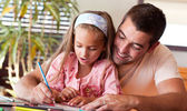 Happy father helping her daughter for homework — Foto Stock