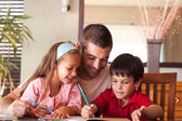 Smiling father helping his children for homework — Stock Photo