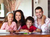 Nice parents helping their children for homework — Stock Photo