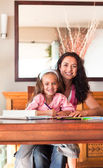 Cheerful mother helping her daughter for homework — Foto Stock