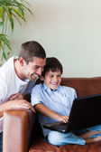 Father and son playing with a computer — Stock Photo