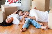 Familie in ein neues haus auf boden liegend mit boxen — Stockfoto