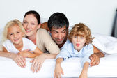 Happy family together on bed — Stock Photo