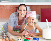 Lovely mother and her daughter baking in a kitchen — Foto de Stock