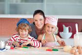 Joyful mother baking with her children — Stock Photo