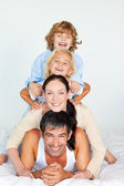 Cheerful family lying on a white bed — Stock Photo