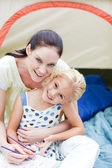 Mother and daughter playing in tent — Stock Photo