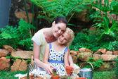 Joven madre e hija plantando flores — Foto de Stock
