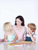 Mutter ihren kindern hausaufgaben helfen — Stockfoto