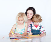 Mother and children writing together — Stock Photo