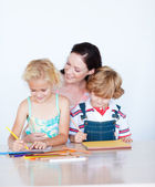 Mother painting with her children — Photo