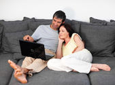 Lovely couple using a laptop on a sofa — Stock Photo