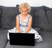 Young girl using a laptop on a sofa — Foto Stock
