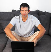 Happy man using a laptop on a grey sofa — Stock Photo