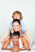 Family playing in bed with thumb up — Stock Photo