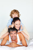 Family having fun in bed with thumbs up — Stock Photo