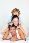 Parents and son playing in bed — Stock Photo