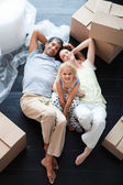 Parents and daughter on the floor with a lot of boxes — Stock Photo