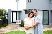 Newlyweds with their new house — Stock Photo