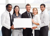 Business team holding a blank card — Stock Photo