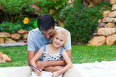 Father and daughter reading in a park — Stock Photo