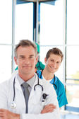 Smiling young doctor in focus in a line with copy-space — Stock Photo