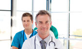 Friendly young doctor in focus in a line — Stock Photo