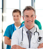 Portrait of a mature doctor leading his team — Stock Photo
