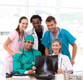 Medical team examining an X-ray and smiling at the camera — Stock Photo