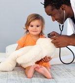 Children's doctor exams a little girl with stethoscope — Stock Photo