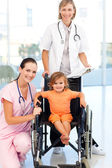 Little girl in a wheelchair doctors looking at the camera — Stock Photo