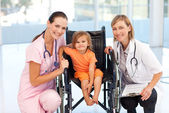 Baby in a wheelchair with nurse and doctor — Stock Photo