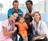 Group of doctors with a baby in a wheelchair — Stock Photo