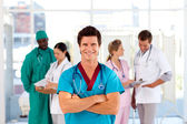 Attractive doctor with is team in the background — Stock Photo