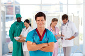 Smiling doctor with his team in the background — Stock Photo