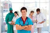 Leende läkare med sitt team i bakgrunden — Stockfoto
