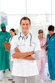 Medico giovane e sorridente con il suo team in background — Foto Stock