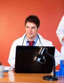 Atractivo doctor usando una laptop en oficina — Foto de Stock