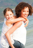 Mother giving daughter piggyback ride on the beach — Stock Photo