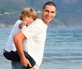 Father giving his son piggyback ride on the beach — Stock Photo