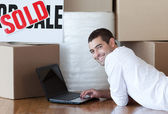 Attractive man lying on the floor using a laptop — Stock Photo