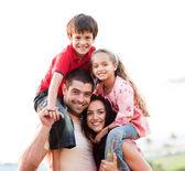 Föräldrar att ge barn piggyback rider — Stockfoto