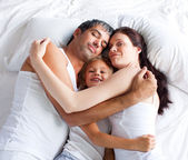 Little gril relaxing on bed with her parents — Stock Photo