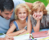 Smiling children drawing with their father — Stockfoto