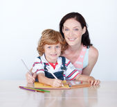 Son and mother drawing looking at the camera — Stock Photo