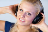 Blonde woman listening music with headphones — Stock Photo